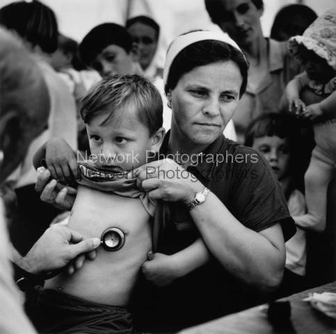 Kind wird von Sanitätern am Flughafen von Tuzla untersucht. Juli 1995.