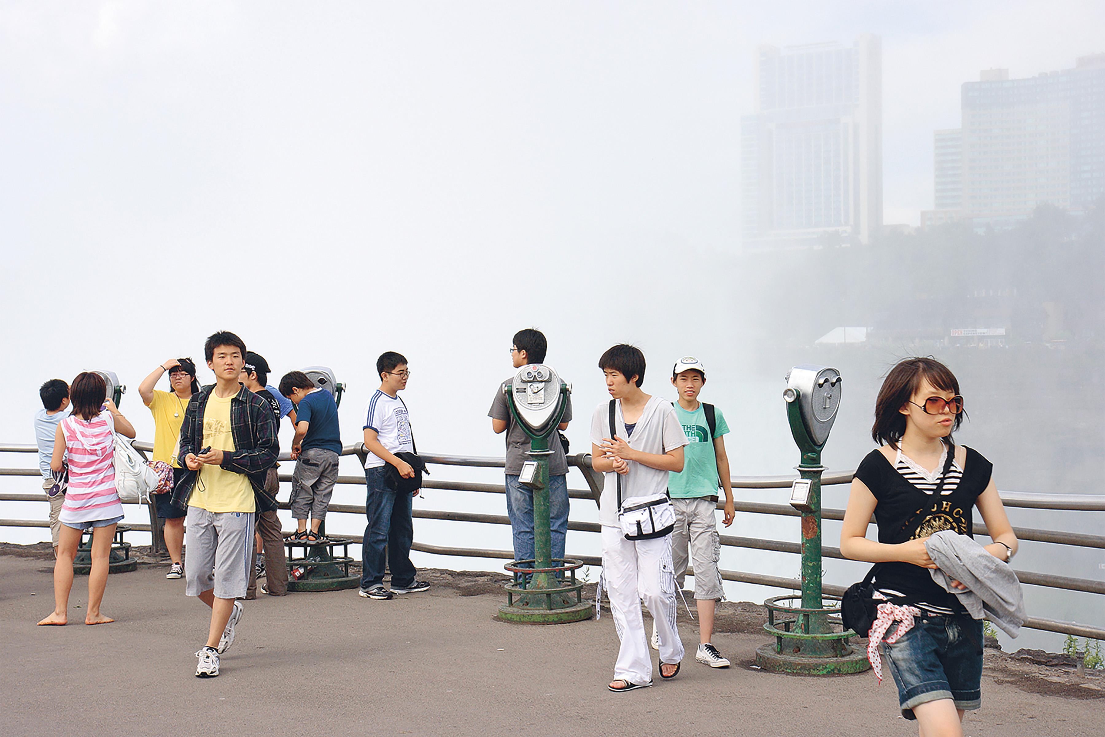 Menschen auf einer Aussichtsplattform, die zu sehene Skyline im Nebel